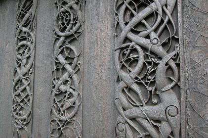 1200px-Carvings_in_north_wall_portal2C_Urnes_Stave_Church-1
